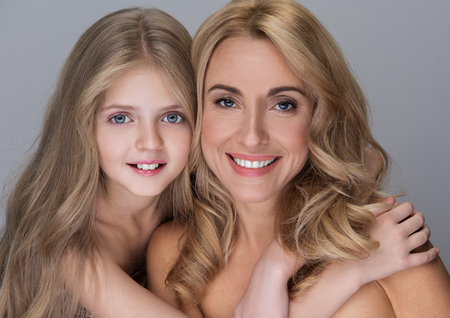 Photo pour My best mom. Portrait of cute little daughter is hugging her charming middle-aged mother while standing together and sharing their love. They are looking at camera with smile. Isolated background - image libre de droit