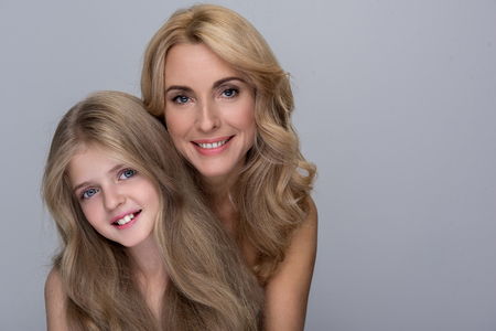 Photo pour Happy together. Portrait of cheerful gorgeous mother and daughter are standing together while looking at camera with joy. Isolated background with copy space in the right side - image libre de droit