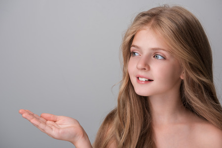 Foto de Look here. Joyful pretty girl with long hair is looking aside with smile while holding out her hand palm up. Isolated background with copy space in the left side - Imagen libre de derechos