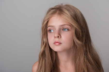 Foto de Feeling lonely. Serious little girl is standing and looking aside wistfully. Isolated background - Imagen libre de derechos