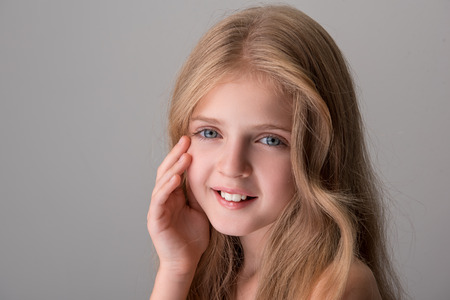 Young and beautiful. Portrait of joyful pretty little girl with long hair and naked shoulders is standing and looking at camera with smile while touching her face. Isolated background with copy space