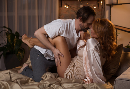 Foto de Side view of passionate middle-aged loving couple hugging while lying on bed. Man is touching female leg while expressing his desire - Imagen libre de derechos