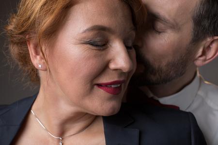 Foto de Close up of happy woman face smiling while man is kissing her cheek with gentleness - Imagen libre de derechos