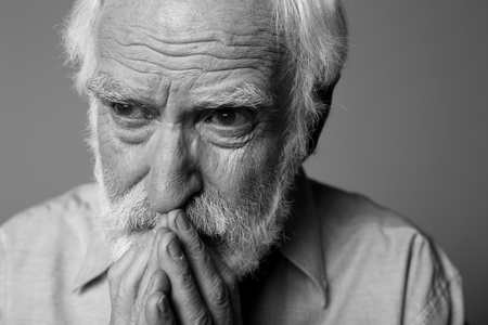 Photo pour Close up black-and-white portrait of aged distressed pensioner expressing sorrow. Isolated on grey background - image libre de droit