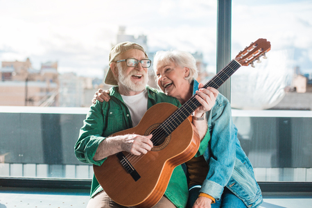 Foto de Musical holiday. Waist up portrait of amorous married man and woman enjoying playing on instrument - Imagen libre de derechos