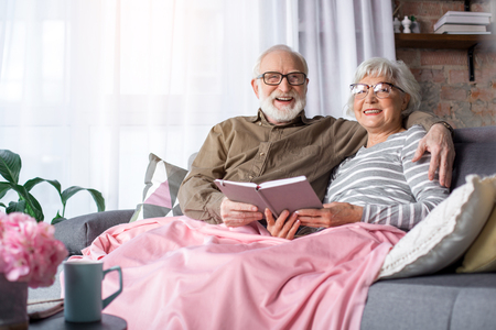 Photo pour Portrait of lovely married old couple relaxing on couch with pillows at home. Man is hugging woman while they are looking at camera and laughing - image libre de droit