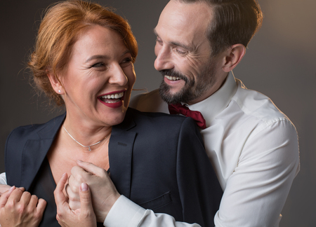 Foto de Portrait of joyful loving mature couple hugging and laughing. Caring gentleman is giving his jacket to lady with fondness. Isolated - Imagen libre de derechos