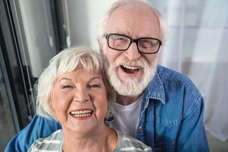 Photo for Having fun. Waist up portrait of old family bursting with laugh at living room. Man is embracing woman from behind - Royalty Free Image
