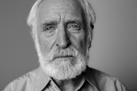 Foto de Close up black-and-white portrait of sorrowful man looking at camera while standing. Isolated on grey background - Imagen libre de derechos