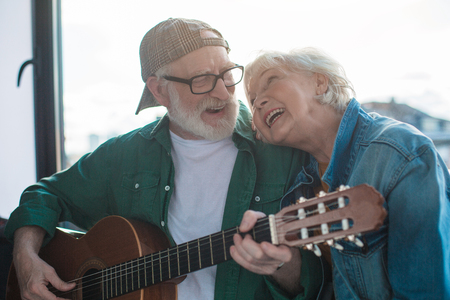 Photo pour Favorite song. Portrait of two happy pensioners looking to each other with love. Man is playing on musical instrument - image libre de droit