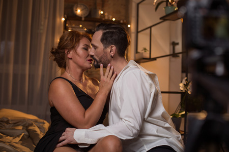 Photo for Impassionate loving couple is kissing and hugging with desire in bedroom. Camera is recording their intimacy - Royalty Free Image