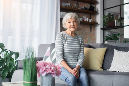 Photo pour Portrait of mature woman resting on comfortable couch at home. She is smiling and looking at camera - image libre de droit