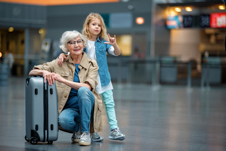 Photo pour My best friend. Full length portrait of trendy optimistic senior grandmother is squatting and resting on suitcase in airport while her grandchild is hugging her for shoulders. Copy space in right side - image libre de droit