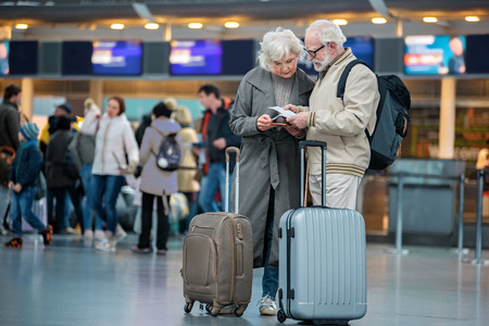 Photo pour Checking trip details. Full length of serious senior wife and husband are standing with suitcases at international airport and looking at flight tickets with concentration. Copy space in left side - image libre de droit