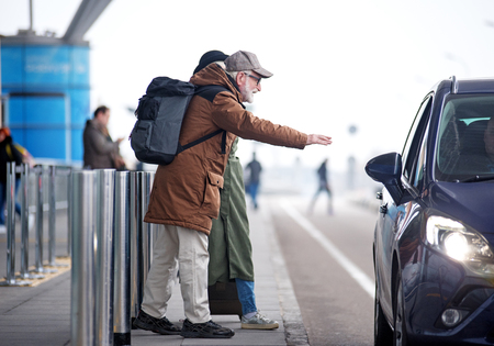 Foto de Need transport. Full length side view of senior couple is standing near road. Profile of positive bearded old man in glasses and with backpack is raising hand while stopping car - Imagen libre de derechos