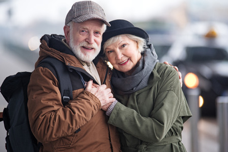 Foto de My biggest love. Waist up portrait of cheerful senior man with backpack and elegant woman are standing on street and hugging each other with pleasure. They are looking at camera with smile - Imagen libre de derechos