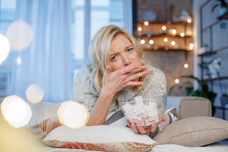 Photo for Portrait of young lady trying to eat lot of marshmallows. Garland is behind her. Copy space in left side - Royalty Free Image