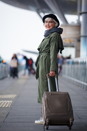 Foto de Ready to travel. Full length of positive senior woman wearing hat is standing outdoors with suitcase while looking at camera with joy. She is locating at international airport - Imagen libre de derechos