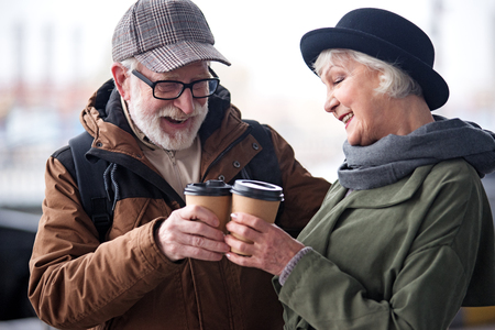 Foto de Full of love. Charming senior woman and man are standing outdoors. They are drinking coffee and enjoying time together while having pleasant conversation - Imagen libre de derechos