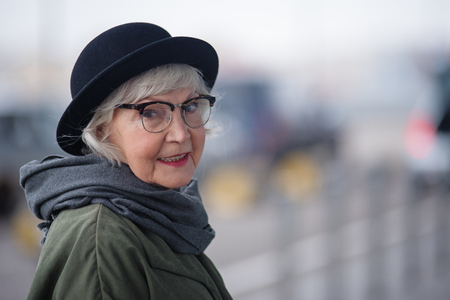 Foto de Pleasant lady. Portrait of charming stylish senior female in glasses is standing outside and looking at camera with slight smile. Copy space in the right side - Imagen libre de derechos