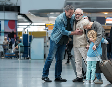 Foto de Happies moment. Full length of aged father is hugging his adult sun and expressing gladness. Old joyful woman is embracing her little grandchild while standing in waiting hall at airport. Copy space - Imagen libre de derechos