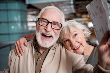 Foto de Happy journey. Portrait of delighted old romantic couple is standing at modern terminal. They are looking at camera with joy. Old man is holding his tickets while senior woman is hugging him - Imagen libre de derechos