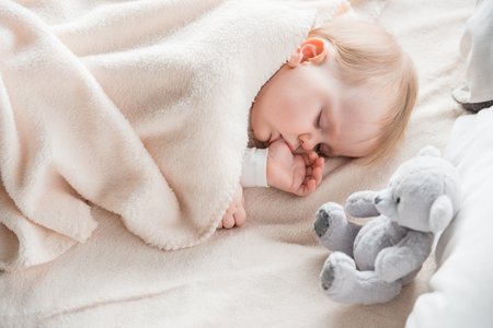 Photo pour Tranquil infant dreaming in the morning on cozy sofa wrapped in soft covering. Teddy bear is on bed - image libre de droit