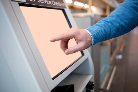 Photo pour Confirm flight details. Close-up of male hands is using self-service check-in kiosk while standing at international airport building. He is registering on his airplane - image libre de droit