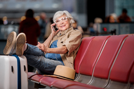 Photo pour Pleasant conversation. Full length portrait of gray-haired lady in glasses is resting on seats at airport lounge while putting feet on suitcase. She is talking on mobile phone with smile. Copy space - image libre de droit