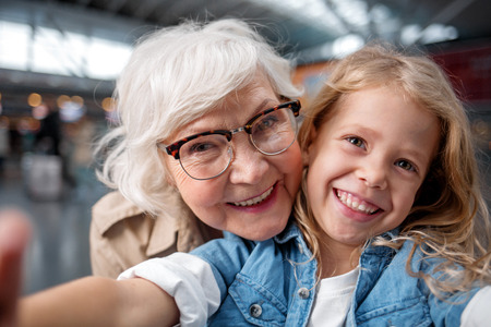 Photo pour Cool picture. Close-up portrait of joyful happy elderly grandmother is taking selfie with her adorable granddaughter. They are looking at camera with wide smile while standing at airport hall - image libre de droit