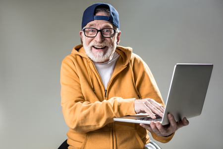Photo pour Waist up portrait of trendy pensioner enjoying the use of new laptop. He is looking at camera with big smile. Isolated on grey background - image libre de droit