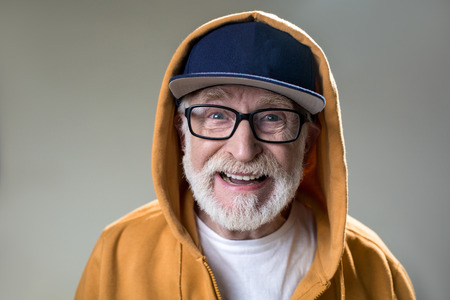 Foto de Portrait of bearded old man with hood dressed over the cap. His face expressing positivity. Isolated on grey background - Imagen libre de derechos