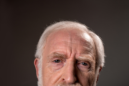 Photo pour Close up of gray haired male half face wrinkling his forehead, expressing tiredness. Isolated on grey background - image libre de droit