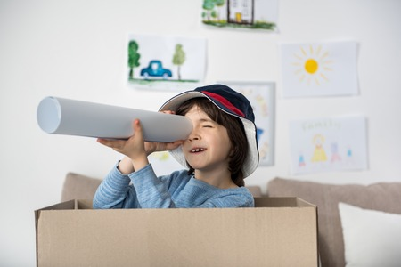 Photo for Portrait of joyful schoolboy standing inside of box and looking through rolled paper. Childish drawings hanging on wall - Royalty Free Image