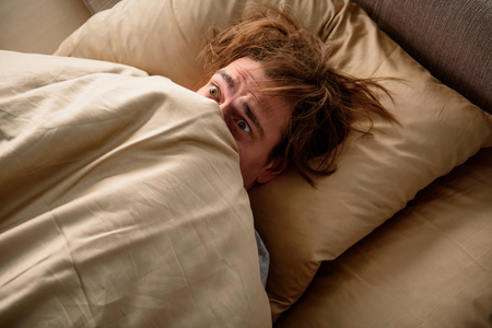 Photo pour Feeling frightened. Scared adult male lying in bed and covering his head with a blanket in bedroom - image libre de droit
