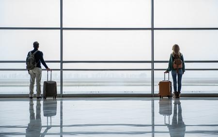 Foto de Unacquainted man and woman standing with bags in different parts of the airport hall - Imagen libre de derechos