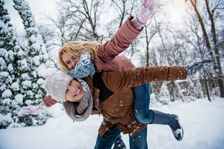 Photo pour We are free. Joyful loving couple is having fun in winter park. Guy is keeping girl on back and laughing. They are stretching arms sideways - image libre de droit