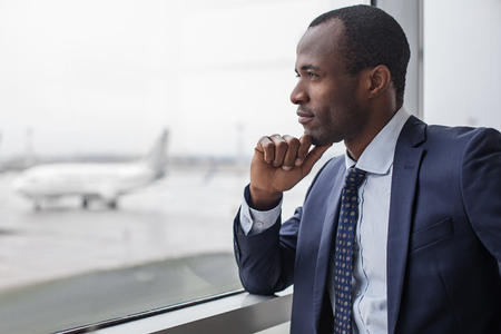 Foto de Lost in thoughts. Profile of pensive young stylish entrepreneur is standing at airport building. He is leaning elbow on window while touching his chin and enjoying view. Copy space in the left side - Imagen libre de derechos