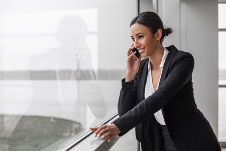 Photo for Involved in communication. Cheerful elegant gorgeous businesswoman is standing in office while leaning on window. She is talking on smartphone while looking through glass with smile. Copy space - Royalty Free Image