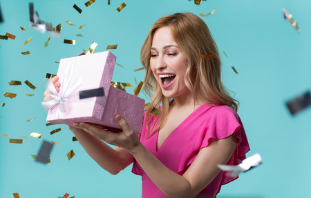 Photo pour What is inside. Curious young woman is looking into present box and laughing with happiness. Holiday celebration concept - image libre de droit