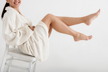 Photo pour Happy women wearing terry robe resting on stool. She is holding up slender feet and smiling. Isolated on background - image libre de droit