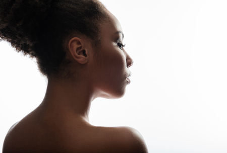 Foto de Close up profile of clean woman face with soft skin. She is looking with tranquility. Copy space on right side. Isolated on background - Imagen libre de derechos