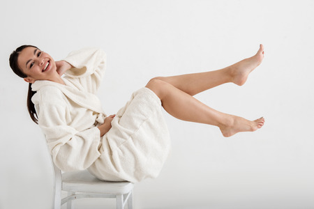 Foto de Satisfied girl in bathrobe sitting on chair and showing her fit legs. Isolated on background - Imagen libre de derechos