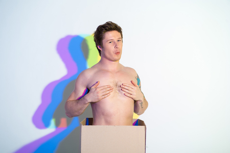 Photo for Portrait of cheerful young male with naked torso covering nipples. Delivery and fun concept - Royalty Free Image