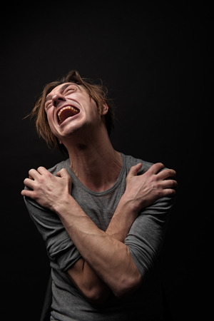 Photo pour Waist up portrait of frustrated junkie sitting with arms crossed on chest, he is looking up and crying. Isolated on background - image libre de droit