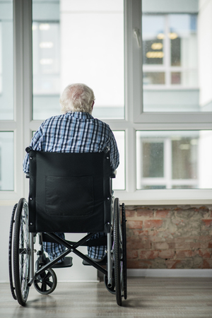 Foto de Senior male is sitting in wheelchair in front of the window in room. He is looking outside. Concept of loneliness. Copy space in right side - Imagen libre de derechos
