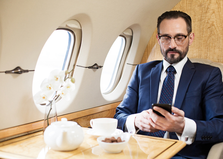 Photo pour Waist up portrait of tranquil middle aged man travelling by plane. He is texting message on mobile phone while sitting - image libre de droit