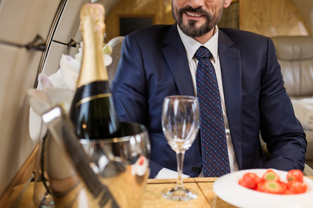 Foto de Smiling bearded male sitting in airplane seat at tray table with champagne and strawberry. Focus on man - Imagen libre de derechos