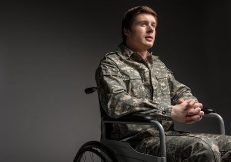Foto de Cheerful disabled young military man looking up with hope. He is sitting in wheelchair with his hands folded in the lock. Isolated on grey background. Copy space in left side - Imagen libre de derechos