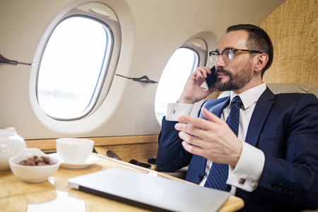 Photo for Tranquil solid businessman sitting in first class seat of airliner, he is talking by cellphone and gesticulating - Royalty Free Image